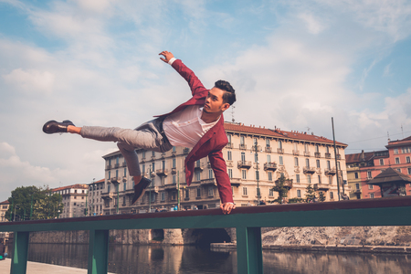 philippine adult: Young handsome Asian model dressed in red blazer jumping a balustrade