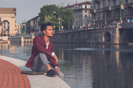 philippine adult: Young handsome Asian model dressed in red blazer sitting by an artificial basin Stock Photo