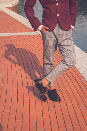 philippine adult: Shadow of an Asian model dressed in red blazer posing by an artificial basin