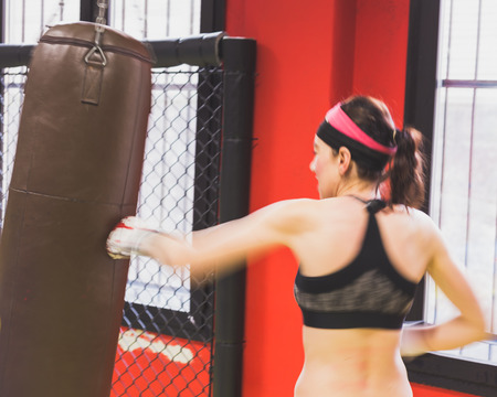 strenght: Beautiful young girl boxing against punching bag in the gym (intentionally blurred). Concept of strenght and fitness. Stock Photo