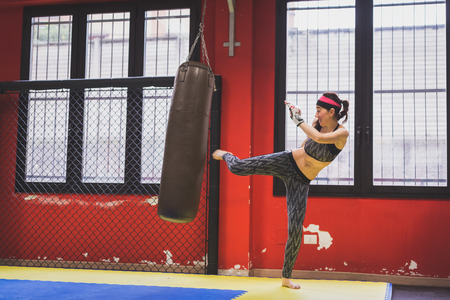 strenght: Beautiful young girl boxing against punching bag in the gym. Concept of strenght and fitness.