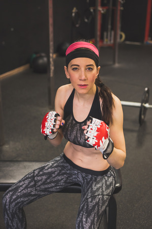 strenght: Portrait of a beautiful young girl wearing boxing gloves in the gym. Concept of strenght and fitness.