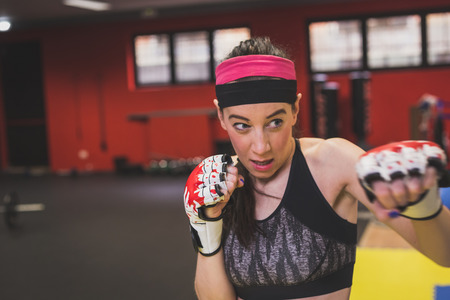 strenght: Beautiful young girl boxing in the gym. Concept of strenght and fitness.