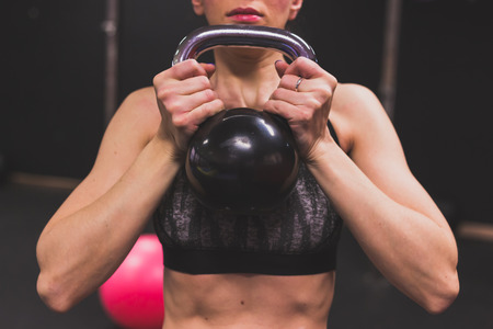 strenght: Detail of a beautiful young girl doing workout in the gym. Concept of health and fitness. Stock Photo