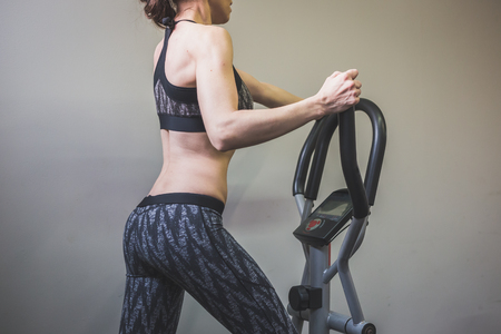 Beautiful young girl doing workout in the gym. Concept of health and fitness.