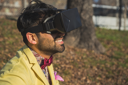 Portrait of an Indian young handsome man wearing virtual reality headset in a city park