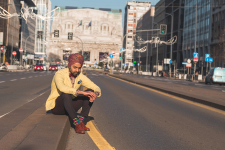 indian style sitting: Portrait of an Indian young handsome man posing in an urban context Stock Photo