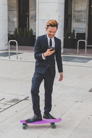 ni�o en patines: Modelo asi�tico hermoso joven vestido con traje oscuro y corbata mensajes de texto en las calles de la ciudad