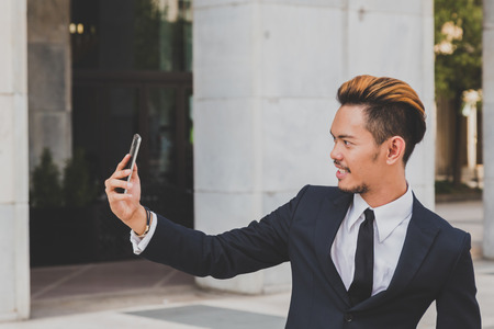 asian style: Young handsome Asian model dressed in dark suit and tie taking a selfie in the city streets