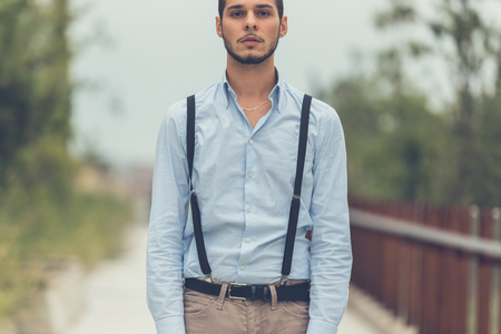 suspenders: Young handsome man with short hair and beard wearing suspenders and posing in an urban context Stock Photo
