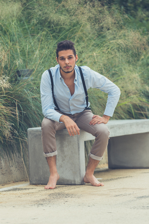 young man short hair: Young handsome man with short hair and beard wearing suspenders and  sitting on a concrete bench
