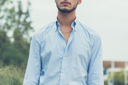 uomini belli: Giovane uomo bello con i capelli corti e la barba che porta bretelle e in posa in un contesto urbano Archivio Fotografico