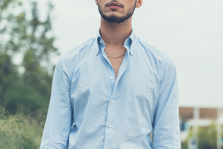 beautiful boys: Young handsome man with short hair and beard wearing suspenders and posing in an urban context Stock Photo