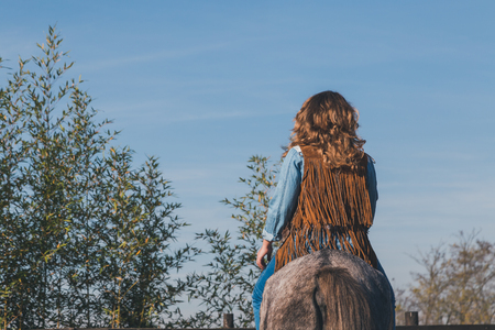 horse blonde: Back view of a blonde girl riding a horse