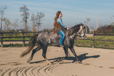 stride: Pretty blonde girl riding her grey horse in the countryside