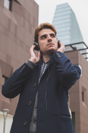 alone boy: Young handsome man with headphones listening to music in an urban context Stock Photo
