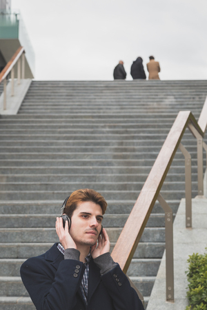 boy alone: Young handsome man with headphones listening to music in an urban context Stock Photo