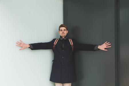 ni�o con mochila: Hombre hermoso joven que presenta en un contexto urbano Foto de archivo