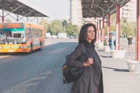 persona triste: Joven y bella morena con el pelo largo que presenta en un contexto urbano