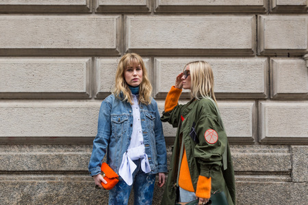MILAN, ITALY - FEBRUARY 26: Two fashionable young women pose outside Sportmax fashion show during Milan Women's Fashion Week on FEBRUARY 26, 2016 in Milan.