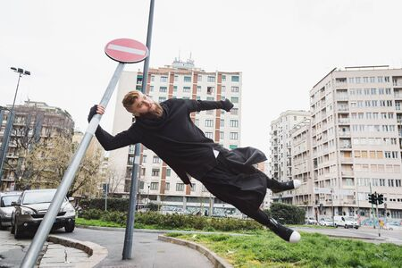context: Stylish young bearded man jumping in an urban context Stock Photo