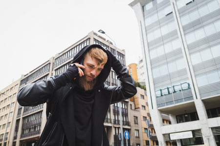 beautiful boys: Stylish young bearded man talking on phone in an urban context