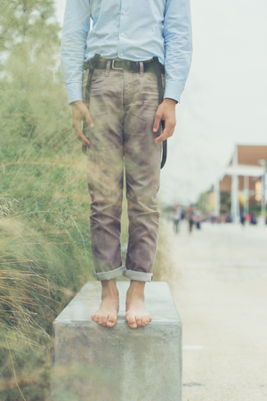 bare feet boys: Detail of a young man wearing suspenders and posing in an urban context
