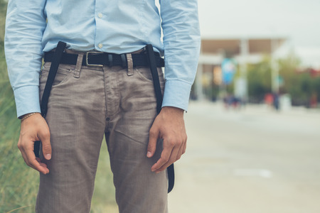 suspenders: Detail of a young man wearing suspenders and posing in an urban context
