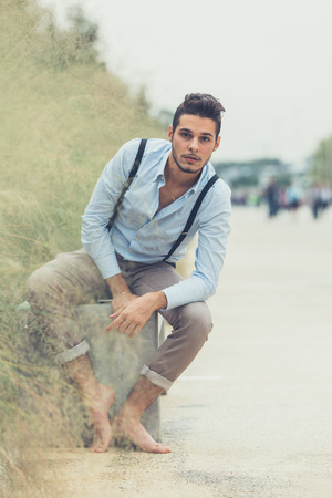 bare feet boys: Young handsome man with short hair and beard wearing suspenders and posing in an urban context Stock Photo
