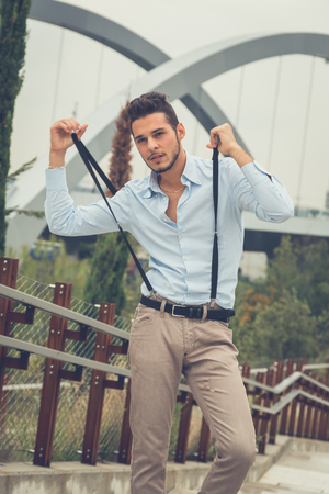 young man short hair: Young handsome man with short hair and beard wearing suspenders and posing in an urban context Stock Photo