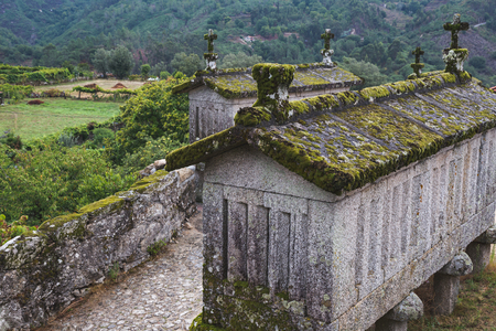 drier: SOAJO, PORTUGAL - AUGUST 28, 2015: Typical granite stone granaries called Espigueiros, raised from the ground by pillars to avoid the access of rodents.
