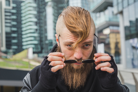 context: Stylish young bearded man posing in an urban context