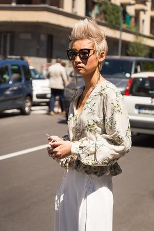 mens fashion: MILAN, ITALY - JUNE 20: Fashionable woman poses outside Etro fashion show building during Milan Mens Fashion Week on JUNE 20, 2016 in Milan.
