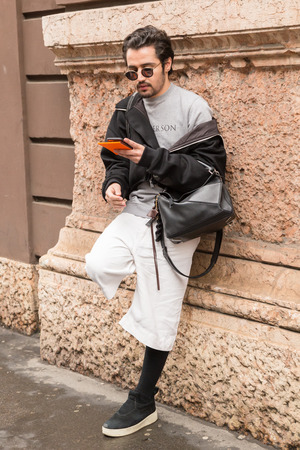 MILAN, ITALY - FEBRUARY 24: Fashionable man poses outside Sportmax fashion show during Milan Womens Fashion Week on FEBRUARY 24, 2017 in Milan.