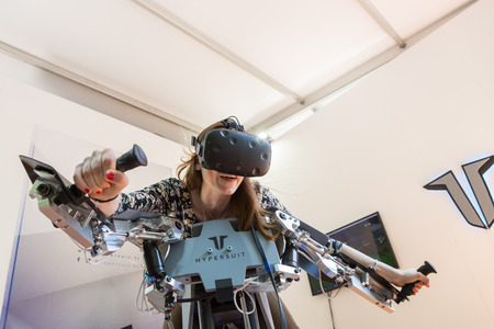 MILAN, ITALY - MAY 26: Girl tries virtual reality headset and flight simulator at Wired Next Fest, event dedicated to future, innovation and creativity on MAY 26, 2017 in Milan.