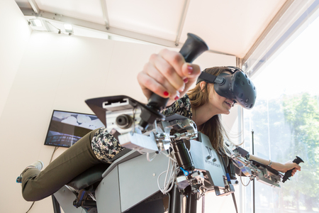htc: MILAN, ITALY - MAY 26: Girl tries virtual reality headset and flight simulator at Wired Next Fest, event dedicated to future, innovation and creativity on MAY 26, 2017 in Milan.