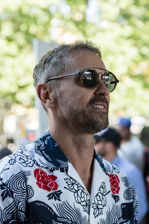 MILAN, ITALY - JUNE 17: Fashionable man poses outside Neil Barrett fashion show during Milan Mens Fashion Week on JUNE 17, 2017 in Milan.