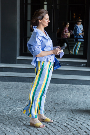 MILAN, ITALY - JUNE 17: Fashionable woman poses outside Neil Barrett fashion show during Milan Mens Fashion Week on JUNE 17, 2017 in Milan. Editorial