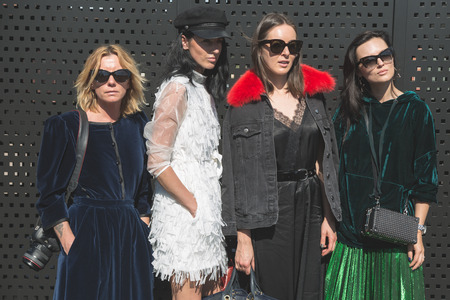 MILAN, ITALY - SEPTEMBER 20: Fashionable women pose outside Gucci fashion show building during Milan Womens Fashion Week on SEPTEMBER 20, 2017 in Milan.