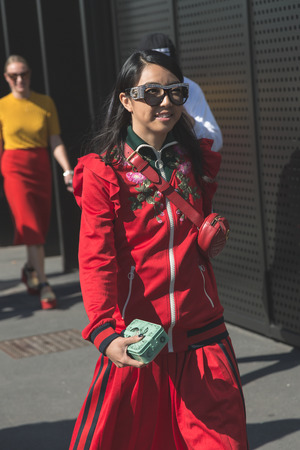 MILAN, ITALY - SEPTEMBER 20: Fashionable woman poses outside Gucci fashion show building during Milan Womens Fashion Week on SEPTEMBER 20, 2017 in Milan.