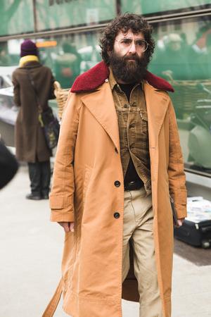 MILAN, ITALY - JANUARY 15: Fashionable man poses outside Armani fashion show during Milan Mens Fashion Week on JANUARY 15, 2018 in Milan.