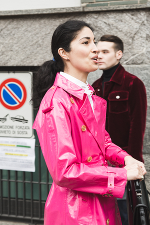 MILAN, ITALY - JANUARY 15: Fashionable woman poses outside Armani fashion show during Milan Mens Fashion Week on JANUARY 15, 2018 in Milan.