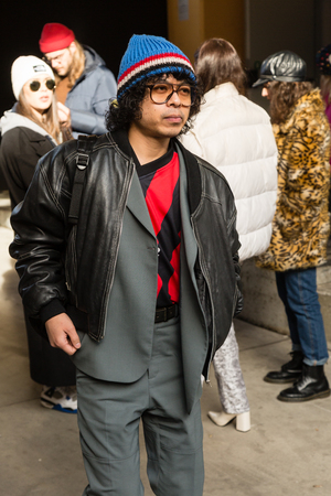 MILAN, ITALY - JANUARY 12: Fashionable man poses outside Magliano fashion show during Milan Mens Fashion Week on JANUARY 12, 2019 in Milan. Editorial