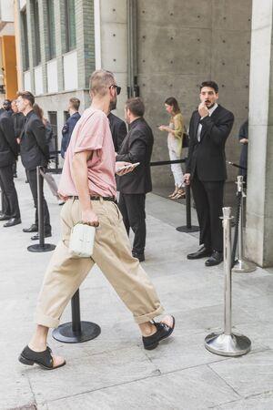 MILAN, ITALY - JUNE 15: Fashionable man poses outside Armani fashion show during Milan Mens Fashion Week on JUNE 15, 2019 in Milan.