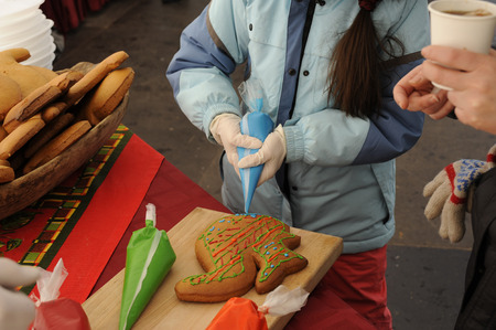 extrusion: Girl decorate gingerbread colored glaze pastry bag