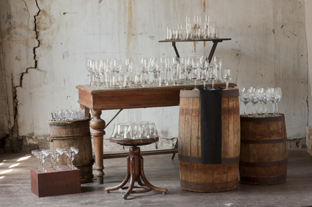 sommeliers: empty glass stand in rows on the drums, tables, stools and boxes