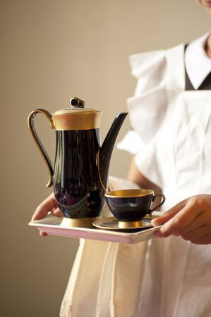 sirvientes: manos de empleada sostiene una bandeja con una taza de caf� y la taza Foto de archivo