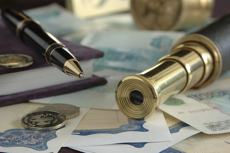bank notes: still life of a ballpoint pen, a telescope bank notes and coins