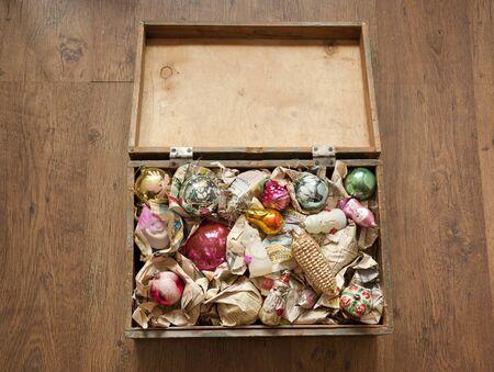juguetes antiguos: caja de madera de los viejos juguetes de Navidad envueltos en papel de periódico