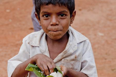 hunger: Indian village boy eats rice arms